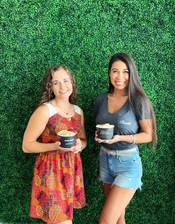 Two women with acai bowls with green backdrop