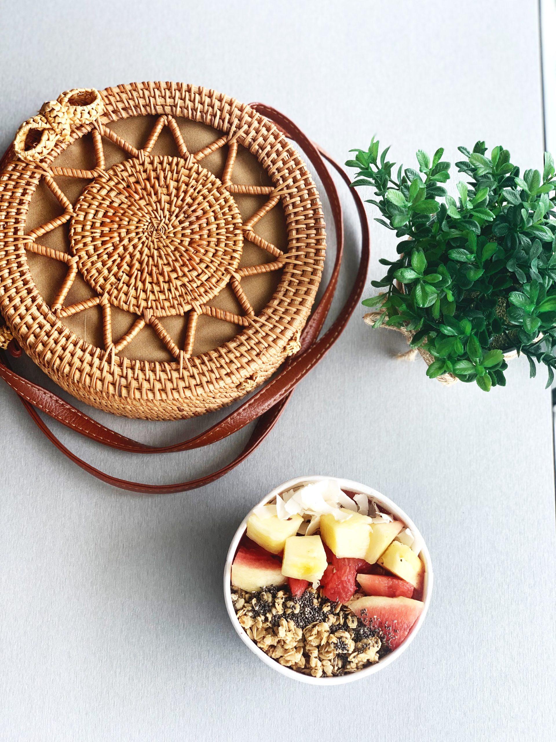 Flat lay of purse, greenery, and acai bowl